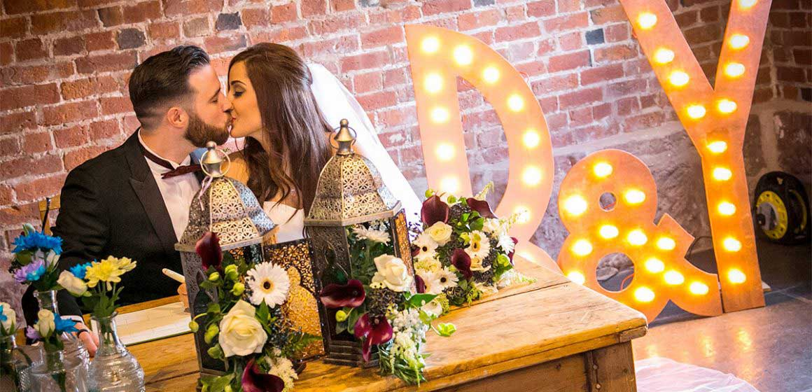 Bride and groom kiss while signing the register after their ceremony